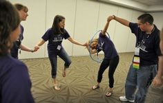 Students race to pass a hula hoop around each other while holding hands as they play cooperative games while participating in the Building Leaders And Strong Tomorrows