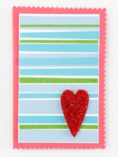 A simple pink card trimmed with decorative-edge scissors serves as the base for this project. Top a slightly smaller rectangle of white cardstock with strips of ribbon and colored paper. A cutout heart decorated with red glitter and adhered with hot glue adds a finishing touch. Editor's Tip: Use sparkly or shimmery ribbon in lieu of strips of glittered paper. Your project will be less of a mess to make, give, and clean up after. Rhinestones also add a bit of bling.