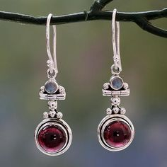 Rich red garnet glows from a sterling silver sky. Bhavesh in India presents an original pair of dangle earrings featuring the unique presence of rainbow moonstone.  Made in India