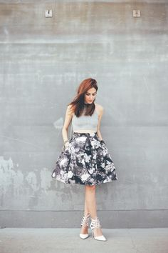 Rock chic outfit wearing midi floral skirt and gray top. Accessories in white with clutch and lace up heels. Also wearing black choker and mix of bracelets.