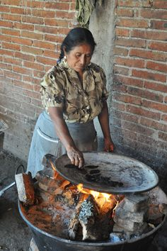 A woman toasts chiles on a comal in a small Zapotec village near Oaxaca city.  She will later grind the chiles to a fine paste using her metate and mano, then add masa to make the famous mole amarillo.  (It was delicious)
