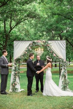 Romantic outdoor Garden Wedding ceremony in Arizona under a rustic arch draped in flowers and greenery