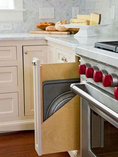 Top 10 Kitchen Cabinetry Trends  narrow spaces that would otherwise have false cabinet fronts utilized as customized spots for pans such as cookie sheets and muffin tins