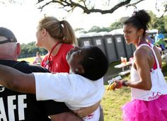 Unique Roden, right, looks on as her partner Nikki Tripplett is carried by medical personnel after collapsing in a shower, after the first day of the Avon 39 walk, Saturday, April 23, 2016, in Houston. Tripplett, a breast cancer patient, had unforeseen side-effects after stopping a medication before an upcoming right mastectomy and hysterectomy.