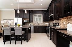 Love the dark expresso cabinets with the light tile floor.