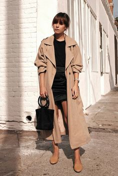 How To Weazr A Trench Coat This Year: Fashion blogger 'Teetharejade' wearing an oversized trench coat, a black t-shirt, a black silk mini skirt, beige mules and a black bucket bag. #trenchcoat #ss18 #springstyle #streetstyle #stylish #fashion2018 #fashiontrends2018 #ootd #outfitideas #outfitinspiration #casualstyle #gingham spring casual outfit, trench coat outfit