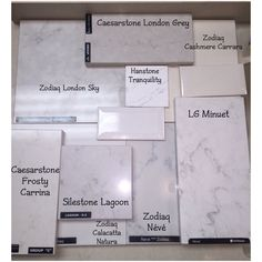 Various Quartz Countertop Samples:  Zodiaq London Sky, Zodiaq Neve, Zodiaq Cashmere Carrara, Zodiaq Calacatta Natura, LG Minuet, Hanstone Tranquility, Caesarstone London Grey, Caesarstone Frosty Carrina; shown with white beveled crackle tile and a creamy colored tile.
