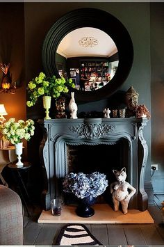 dark walls, black convex mirror, eclectic mantlescape, and bookshelves in the distance. Black Wall Mirror, Faux Fireplace, Black Fireplace, Fireplace Mirror, Fireplace Ideas, Fireplace Makeovers, Country Fireplace, Craftsman Fireplace, Vintage Fireplace