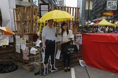 HONGKONG-CHINA/ A woman poses with a cutout of Chinese President Xi Jinping and a yellow umbrella, symbol of the Occupy civil disobedience movement, in front of a barricade set up by pro-democracy protesters at Hong Kong's Mongkok shopping district on October 28, 2014, the day marking the one month anniversary of the movement. Hong Kong has been roiled by a tenacious, month-long student-led people's movement demanding full democracy in the former British colony that returned to Chinese rule…