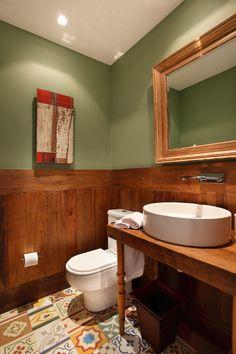 """O novo lavabo ganhou muito mais cor com o piso de ladrilho hidráulico e a pintura em tom verde. Lambris de madeira de demolição revestem parte das paredes e, somados à bancada de madeira da pia, tornam a decoração mais aconchegante. A iluminação também mudou. """"Adicionamos mais pontos de luz e agora a iluminação é feita com lâmpada dicroica"""", explica Paola."""
