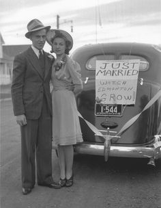 A newly married 1940s Canadian couple pose beside their car