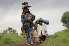 A displaced Congolese family carry their belongings on the road between Rutshuru and Goma, after the village of Kibumba was occupied by an armed militia