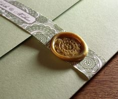 elegant gold custom wax seal with matching belly band on letterpress wedding invitation folio