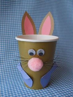 Bunny cup design.  Construction paper for the ears and coat, google eyes, pink pom poms, and cut up a cheap paint brush for the whiskers.