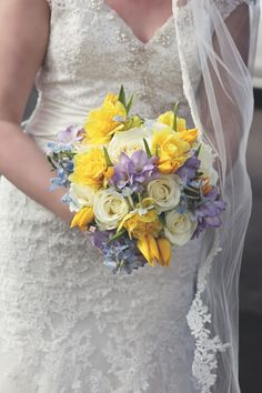 Bright spring bouquet in yellows, whites and blues for a jesmond dene house wedding. with lilac freesia, daffodils, tulips, roses and delphinium. flowers by fleur couture. imageby foto couture