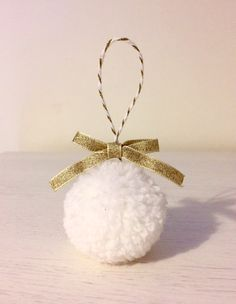 Set of 4 white and gold handmade pom pom bauble tree decorations. Made from acrylic wool, with a gold bow, on white and gold twine. Each pom pom is approximately 5cm in size. This makes a perfect Christmas decoration to hang on your tree or anywhere else. Also available with in silver and white. If you would like to customise the order further please specify at checkout, e.g. cream pom poms with silver bows. Due to the handmade nature the baubles should be handled with care to avoid losing…