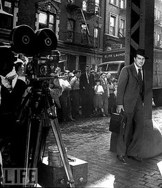 """Ray Milland, leaning on a Third Avenue El post, filming """"The Lost Weekend"""" in NYC in 1945. Neighborhood residents are watching the process. His character, Don Birnam, walks up Third Avenue for many blocks, looking for an open pawn shop to pawn his typewriter so he can buy booze. He finds them all closed because it's Yom Kippur."""