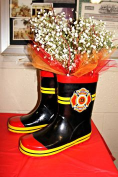 Firefighter Theme. We did this for my Baby Shower... Bought kids boots at Walmart some tinsel at Jo Ann Fabrics & baby's breath. Such a cute idea put it on the cake / dessert table . HLF