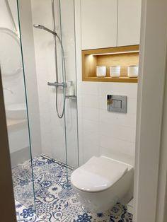 White hexagonal and rectangular tiles. Blue decor hexagonal floor tiles. Wooden shelf with led lights. Modern shower.