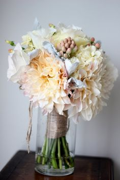 Bouquet of cafe au lait dahlias, cream roses, cream lisianthus, tuberose, hypericum berries, and dusty miller in a twine wrap.