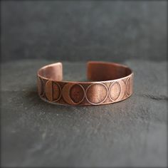 Copper cuff bracelet etched with phases of the moon, from new moon to waning crescent. - To make this etched Copper Cuff Bracelet, I first cut the