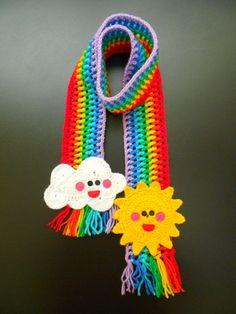 CACHECOL ARCO-ÍRIS: em crochê com lã 100% acrílica.  Listrado nas cores do arco-íris.  Apliques em crochê com motivos de sol e nuvem.  Comprimento: 120 cm. R$ 55,00.