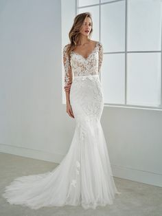 Elegant mermaid wedding dress with a two-piece effect. A dress that streamlines the bride's silhouette and enhances her sensuality with a V-neck, grosgrain waistband and beading. A bodice with an illusion back that blends the skin with the tulle.