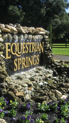 Landscapers are putting the finishing touches on the entrance sign to Equestrian Springs. Lettering is raised off black granite, with water flowing down behind the words.