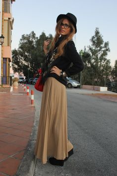 black leather jacket over beige maxi skirt with black scarf, glasses and floppy hat
