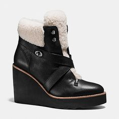 The Kenna Bootie combines the luxury of plush shearling with the sportiness of a roller-bottom wedge in a hand-finished statement design. A crisscross strap secured with an iconic Coach turnlock finishes it with signature style.