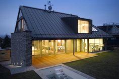 Směrem do zahrady je třípodlažní dům zcela prosklený. Z obývacího pokoje i kuchyně lze vstoupit na terasu