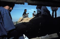 Alex Webb MEXICO. Tijuana, B.C. 1992. Mexicans hanging out around a hole in the border fence prior to trying to cross into the U.S.