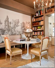 Off the living room is the library with the contemporary table mixed with antique chairs and banquette and grisaille mural.