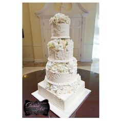 Frosted Art Bakery & Studio 4 tiers -- elevated with fresh flowers. Scroll work and piping on the side with monogram.