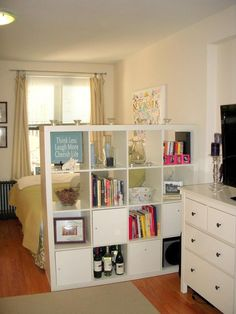 multi purpose furniture. dresser as TV stand and expedit storage unit as a room divider.
