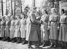 marsalkka Mannerheim tervehtii 14. divisioonan esikunnan lottia. kerrotaan, että Mannerheim hymyili erityisen maireasti kätellessään divisioonan esikunnan kauneimmaksi mainittua lottaa Marjaana Koskelaa Aiheen paikatVienan Karjala, Tiiksa Aiheen aika10.9.1942