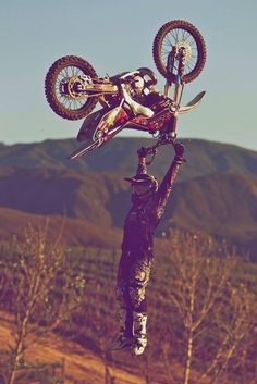 This is a strange picture, because it looks like he is floating and holding his dirtbike above his head.