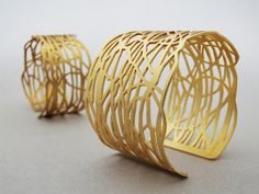 Cuffs | Jenni Caldwell. Handsawn in silver before being goldplated with a matt finish