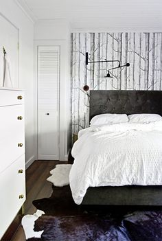 new hardwoods through out layered with cow and sheep hide rugs in the one bedroom via Smitten Studio
