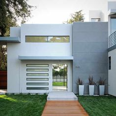 Beautiful, simple, but harmonious front entrance to this house, contrast in materials makes it interesting, while maintaining flow, plants a nice touch.  Particularly like the wooden decking leading to front door.