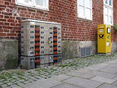 L'artiste allemand Evol peint des immeubles sur du mobilier urbain cubique pour en faire des immeubles miniatures.