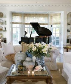 baby grand piano in living room:  love the bay window positioning, the light colored sofas, the coffee table, and the cluster of white/blue ceramics