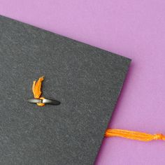 This photo illustrates how to attach the tassle to the mortar board cap using a black fastener.