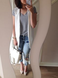 Cropped distressed girlfriend jeans, grey t-shirt, white sleeveless blazer, white handbag and nude heels.