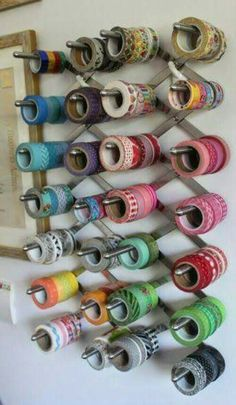 wall-mounted collapsible rack to organize rolls of tape