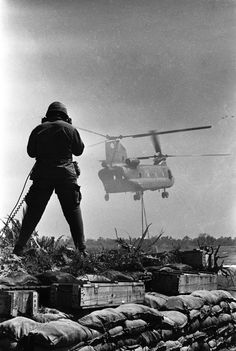 A radio telephone operator guides a Chinook delivering a sling load of materials and supplies at Fire Support Base Pershing, near Dau Tieng