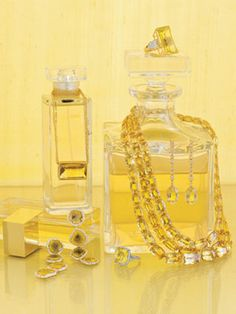 yellow jewelry draped over glass bottles filled with yellow liquid