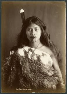 New Zealand, Maori Women Vintage ~ Rotorua, New Zealand. Young Maori woman with moko, wearing a kahu huruhuru (feather cloak), a huia feather in her hair, and a hei tiki (neck pendant), 19th century.