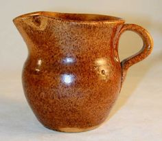 Description: Redware small creamer with an overall mottled brown glaze. The creamer is ovoid in shape with a flat base, rounded sides, with a slightly rounded shoulder. It has a flared neck that termi