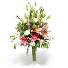 Un mazzo composto da splendidi lilium rosa, rose bianche e varietà di verde. in armonica unione.
